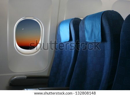 Airplane seat and window inside an aircraft with view of new moon at sunset. - stock photo
