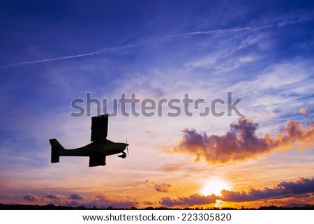 airplane silhouette at sunset - stock photo