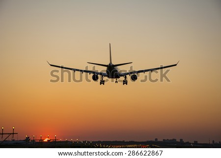 Airplane started landing during sunrise.