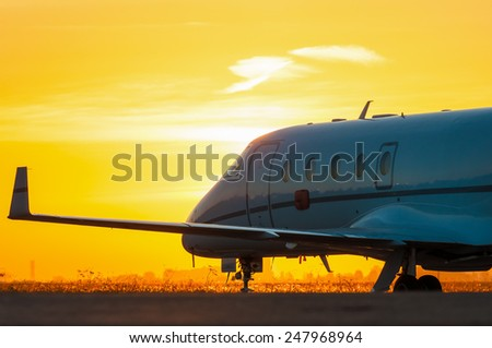 Airplane stay in airport. Business jet on the apron for aircraft. The background of the city - stock photo