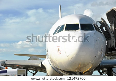 airplane stopped with open door and passengers entering - stock photo