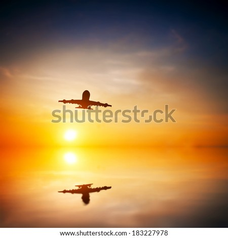 Airplane taking off at sunset. Silhouette of a big passenger or cargo aircraft, airline flying. Abstract water reflection. Transportation - stock photo