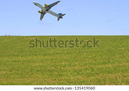 Airplane taking off in a blue sky above green grass - stock photo