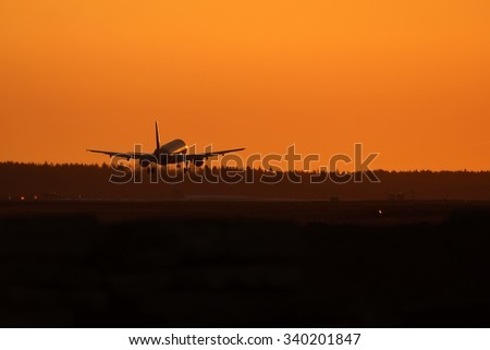 Airplane taxing to runway at dawn.