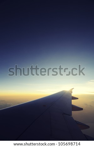 Airplane travel time is sunset, cross process style. - stock photo