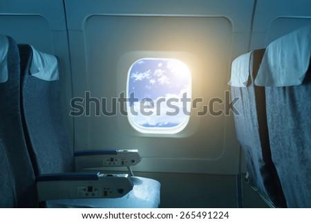 Airplane window against blue sky - stock photo