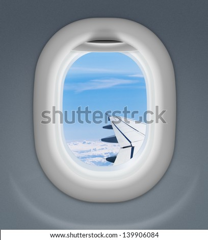 airplane window with wing and cloudy sky behind - stock photo