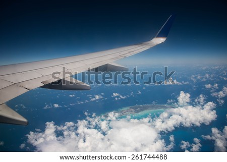 Airplane wing above ocean and Caribbean Island - stock photo