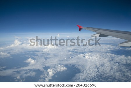 airplane wing above the clouds - stock photo