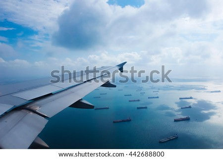 Airplane wing and cargo vessel view on cloudy day - stock photo