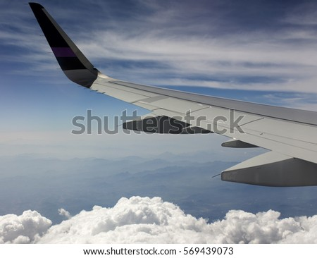 Airplane wing flying, over the clouds
