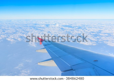 Airplane Wing in Flight from window above clouds and sky. Vintage tone
