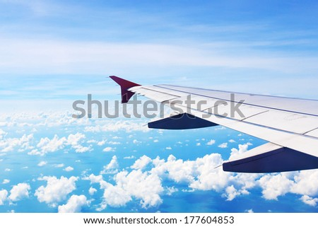 Airplane wing in flight with blue sky