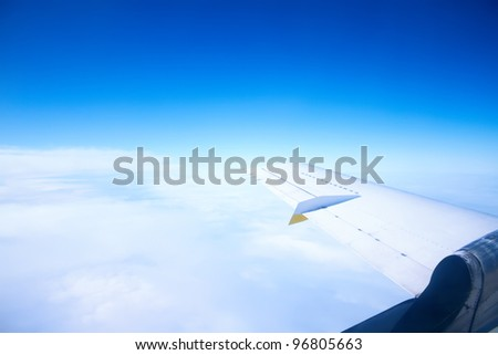 Airplane wing in the blue sky with white clouds