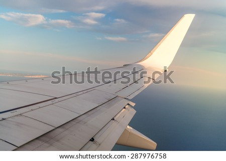 Airplane wing in the sky while flying.