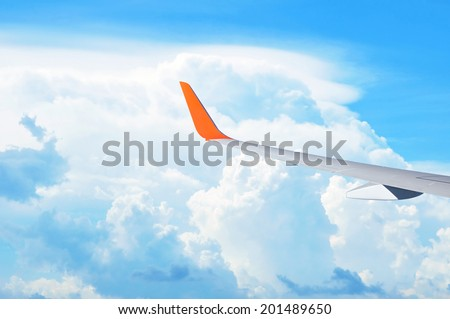 Airplane wing on beautiful blue sky background - tourism & transportation concept - stock photo