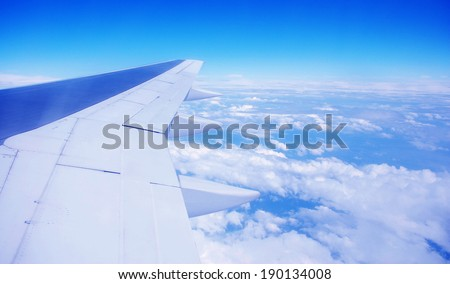 airplane wing on blue clouds  - stock photo