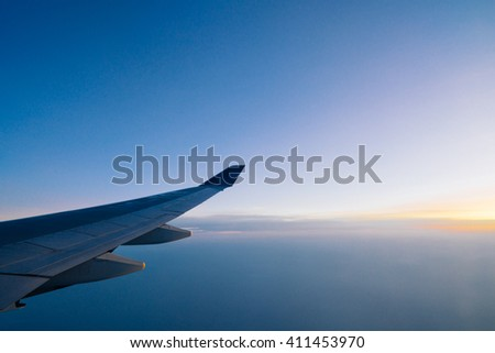 Airplane wing on the dawn sky background