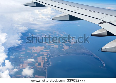Airplane wing out of window above the clouds. Below is the land and sea blue water