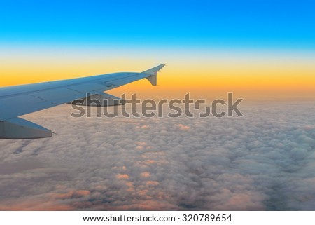 Airplane wing out of window atsunrise time - stock photo
