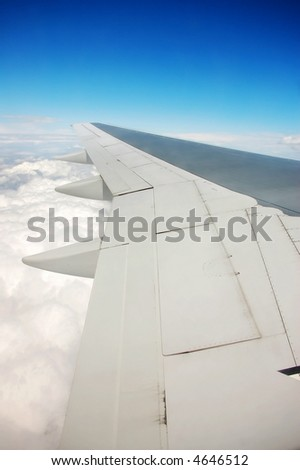 airplane wing over blue sky - stock photo