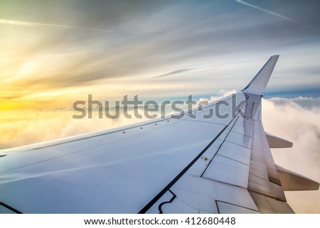 Airplane wing over the beautiful clouds in sunrise. Conceptual theme for travel and holidays