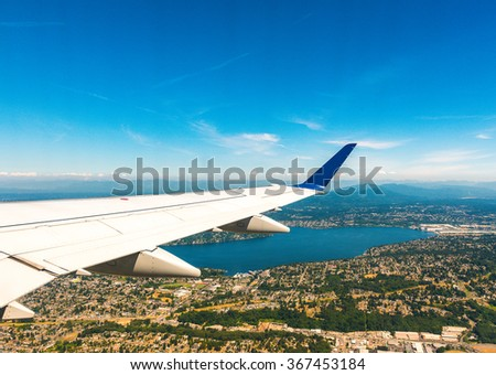 airplane wing over the city with blue sky. - stock photo