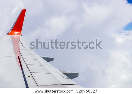 Airplane wing, Sky and cloud as seen through window of an aircraft
