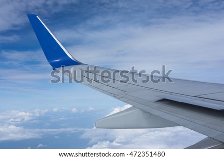 Airplane wing with blue sky in the background
