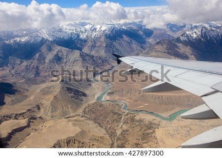 Airplane wing with Leh city and Himalayas mountain