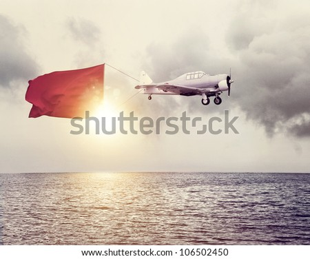 Airplane with a sign above ocean - stock photo