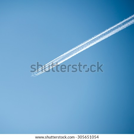 Airplane with contrail high in the sky. - stock photo