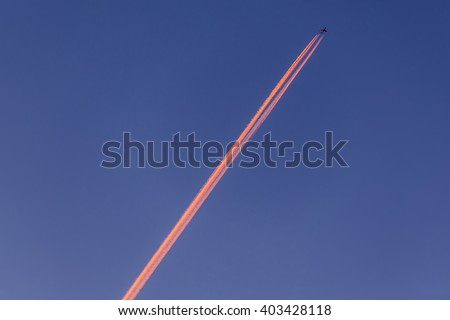 Airplane with contrail high in the sky at sunset. Soft Focus
