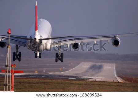 Airplane with four engines landing on runway back view - moments before touchdown - stock photo