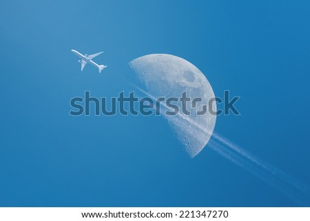 Airplane with Half Moon on a clear blue sky in background, composite - stock photo
