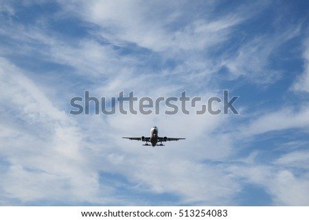 Airplane with landing gear and lights approaching airport.