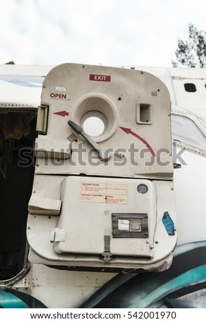 Airplane wreckage white passenger door, taken on a sunny day, useful for plane safety, pilot, flights, air craft, aero space industry, travel, holiday, insurance related concepts