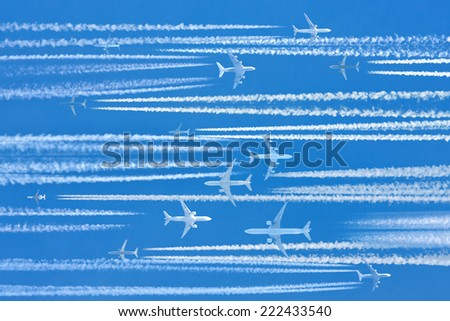Airplanes and contrails on air route caught during busy hours - stock photo