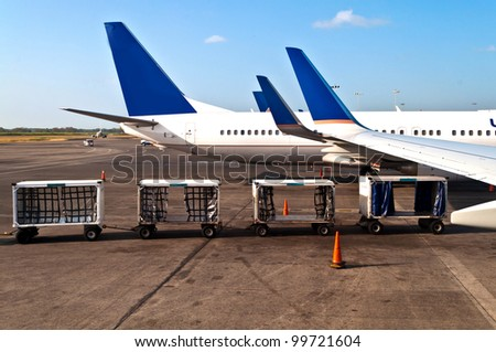 Airplanes on a airplane with luggage cars - stock photo