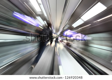 Airport abstract background. Man goes on the escalator. Blurred movement.