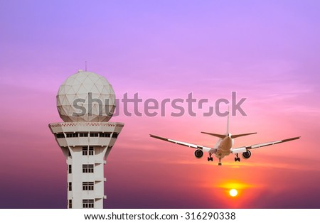Airport control tower and commercial airplane landing at sunset - stock photo