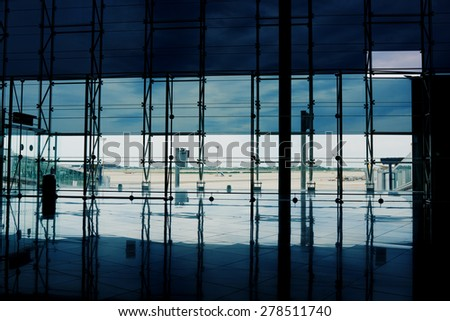 Airport corridor with glassy reflections, windows in departure hall - stock photo