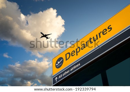 Airport Departure & Arrival information sign with sky - stock photo