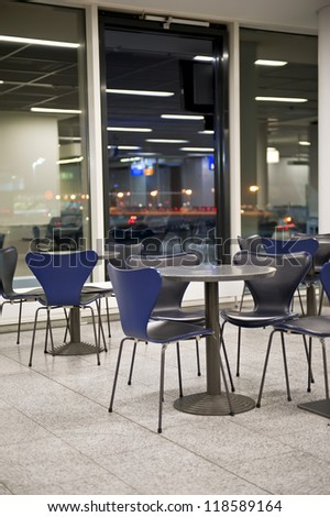 Airport departure waiting area with empty tables and chairs. - stock photo