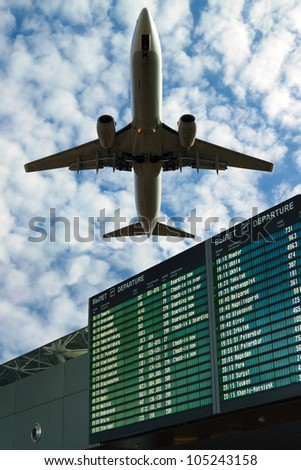 Airport flight information (schedule) with the list of flights in the sky and the plane - stock photo