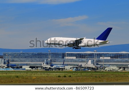 Airport impressions A flying airplane with the airport apron at the background - stock photo