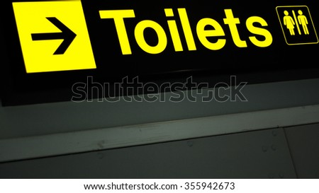 Airport information sign light panel giving directions to toilets in departure lounge for air travelllers.