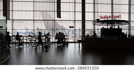 Airport interior with food bar and tourists.
