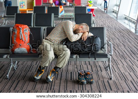 Airport lounge and people waiting for boarding. Body of male on foreground sleeping on his luggage lying in chair other people miscellaneous actions on background terminal interior with large windows - stock photo