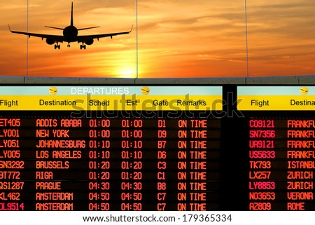 Airport outside window scene with silhouette of plane flying at orange sunset and title of  electronic display timetable of departures  - stock photo